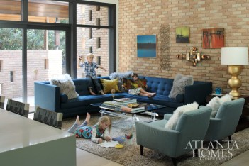 The home's original handmade speckled-glaze brick wall dominates the family room, where Louis, 6, and twins Josephine and Lydia, 7, unwind. A vintage acrylic coffee table from 14th Street Antiques & Interiors serves as the centerpiece. Sectional by Jonathan Adler. Brass wall sculptures from Antiques & Beyond.
