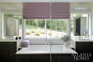 Morris continued the color palette in the master bath with Zoffany wallpaper and a Roman shade in Zimmer + Rohde fabric; it also features a garden tub, floating mirrors and his-and-hers vanities.