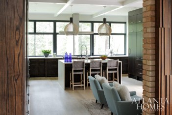 Haute Living Octo hanging lamps are suspended above the kitchen's island, flanked by J. Persing's basketweave bar chairs.