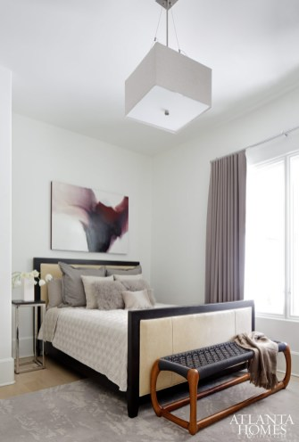 A guest bedroom feels calm and collected-as if you could sink right in. Art from Bill Lowe Gallery. Lighting by Philips Luminaires; custom shade by Julie Witzel Interior Design. Custom window treatments fabricated by J. Lass and Company.