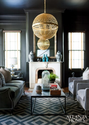 A moody living room/library is punctuated by an Aerin orb pendant with the appearance of gilt-finished rattan.