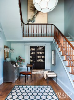 The foyer is painted in a blue-gray shade for a serene aura and punctuated by a Worlds Away honeycomb pendant; just beyond is a painted Belgian apothecary stocked with pewter.