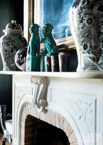 The velvety seating and diamond-pattern rug are foils for more traditional objects, such as foo dogs and ginger jars. The fireplace is one of five in the home.
