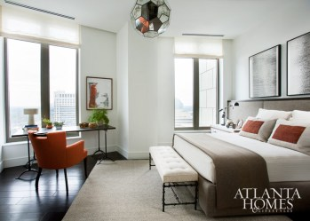 """Although I love neutrals, I find myself attracted to colors that have something to say,"" says Westbrook, who punctuated the neutral-colored guest room with dashes of orange. A series of works by Jeremiah Johnson hangs above a custom-designed upholstered headboard and bedside tables. The room's crowning touch is a mirrored pendant light from Stanton Home Furnishings."