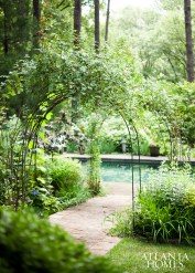 Even the pool deck was treated to a grand entrance; accessed via a pair of French d0ors that spill out on to a pergola-covered terrace, a flowering arbor provides the final passage.