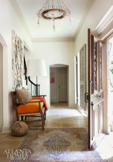An industrial chandelier made by artist/ designer Jeff Jones is a direct counterpoint to the vintage French door and Oriental rug gracing the foyer. Orange mohair on the French bench provides a pop of color.