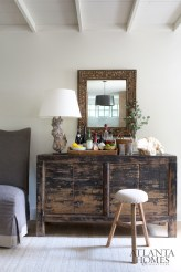 The bright entryway contains a one-of-a-kind Shanxi buffet featuring a heavily distressed finish. The lamp is made from apple wood, while the mirror is an antique.