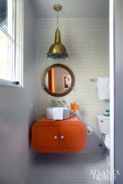 Bold punches of orange filter through Holden's bathroom and bedroom, where unused space above his built-in bunk beds was transformed into a rock-climbing room Lee admits is fun for all ages.