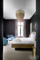 Daughter Madison's bedroom continues the streamlined use of sleek black grasscloth walls and dramatic brass features, such as the pendant light above the bed.