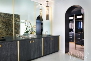White, black and brass accents preside over the master bedroom and bath; cabinets don vintage hardware sourced by Lee.