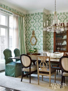 The Brunschwig & Fils wallpaper originally specified for the dining room continues to take center stage, but the mix of chair styles, revamped window treatments and chandelier give the room a layered look.