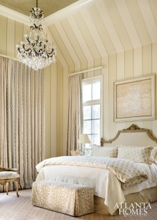 Subtle patterns in the fabrics and striped walls add interest to the monochromatic color scheme in the soothing master retreat. A contemporary painting by Raul Diaz, represented by TEW Galleries, helps anchor the showstopping space.