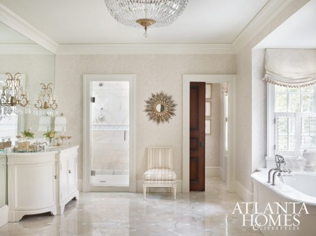 The master bathroom of this townhome is a study in understated luxury with crystal, mirrored glass, Carrara marble and clean white cabinetry.