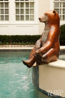 A bronze bear sculpture holds court on one side of the pool.
