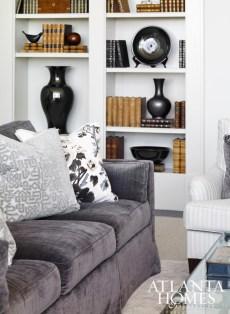 Pattern and texture give a neutral sofa spark, while a built-in bookcase filled with antique books and ceramic pieces adds contrast. Sofa by Cameron Collection in Classic Cloth fabric and ceramics from International Art Properties.