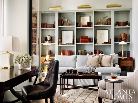 The study, anchored by an artfully filled built-in bookcase, is topped with brass library lamps; a tiger mahogany desk is situated to take advantage of Atlanta skyline views.