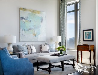 """In the sitting room, a striking piece of art by Jenny Nelson echoes the color of the sky. """"As a former art consultant, I truly believe that art completes a home and gives rooms unique personality,"""" says DeLoach."""