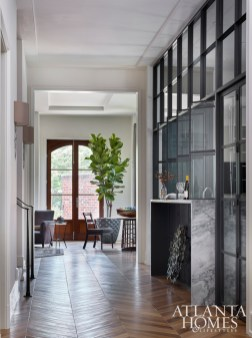 Hardwood floors in a chevron pattern pull the eye down the hallway and into kitchen, where a wall of steel-framed interior windows partition the room from the adjacent spaces without blocking natural light.