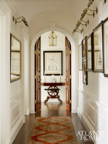 An Oushak from Sullivan Fine Rugs is a striking addition to the hallway of this high-rise. Gallery lighting from Vaughan brings focus to treasured pieces.