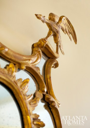 An antique Chippendale mirror adds interest with ornate details.