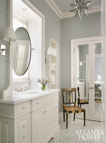 The guest bath features tile and lighting from Waterworks, while a star chandelier from Vaughan echoes the wallpaper by Cowtan & Tout.