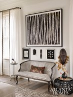An artful vignette displays a painting by Clay McLaurin along with arrowhead collections and African masks.