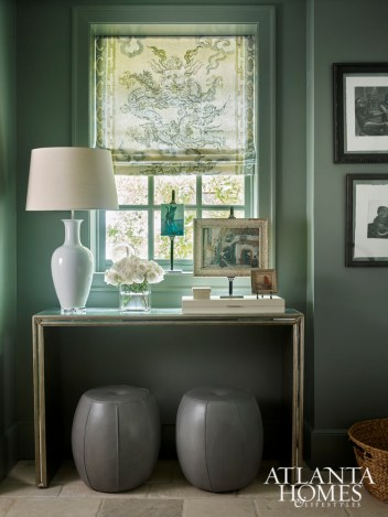 Janie Wilborn wrapped the mudroom in a deep blue-gray hue for a striking effect. An antiqued mirror console and leather stools pull double duty as beautiful accents and—respectively—a place to set down keys and an impromptu stepstool.