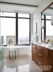 Skyline views are easily accessible in the master bathroom, especially when soaking in the curvy Victoria + Albert tub; both the stone flooring and vanity countertops are by Marmi Natural Stone.
