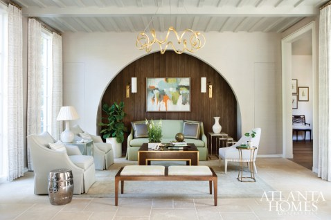 An arched wooden wall anchors the formal living room, where custom upholstered seating from The Charles Stewart Company adds sit-and-stay appeal and an Andrea Costa painting provides pops of color.