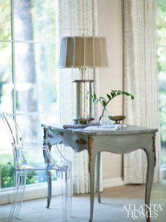 In addition to comfortable seating areas, the formal living room also offers a chic desk space overlooking the leafy neighborhood.