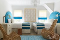 """In Blakely's bedroom, whimsical twig chairs and blue accents impart an """"Alice in Wonderland vibe,"""" says Douglass. The beds are draped with runners from Crate & Barrel. The framed fabric is Kay Douglass Interiors."""