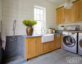 The bluestone from the exterior extends into the laundry room, which has a convenient farmhouse sink and an area to wash off dirty paws after a romp around the large property.