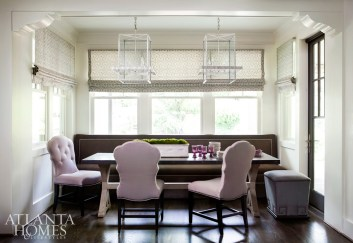 In a dining nook adjacent to the kitchen, a stylish banquette in a warm charcoal wool with nailhead trim offers more tailored, menswear appeal while curvy chairs in a lavender hue add a feminine element to the space. A pair of standout double lanterns from McLain Wiesand illuminate a table with a custom wood base and a zinc top.