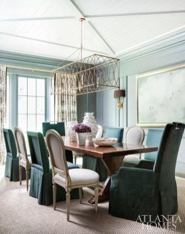 In the dining room, a farm table mixes with contemporary pieces such as the gold metal chandelier by Avrett through R Hughes.