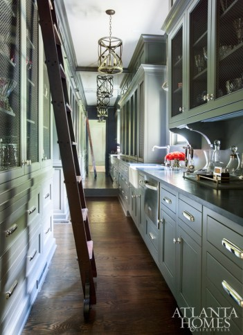 The butler's pantry reveals prized pieces on one ends and hides classic pantry items on the other.