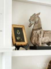Meg Harrington's historic Brookhaven home is brimming with antique treasures from her travels to France, like this antique portrait and horse statue.