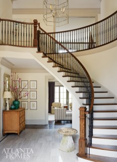 White oak marble was installed as a nod to formal entryways. It's toned down with the lighter, narrow tiles. A Bonny Neiman chandelier adds contemporary drama to the inviting yet formal space.