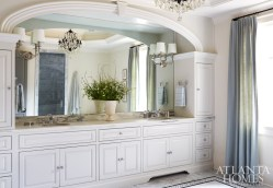 Chris and Karrie requested his and her sinks with an arched frame. Meier sourced a pair of shaded sconces from Progressive Lighting and had them installed directly onto the mirror to help reflect and spread light throughout the room.