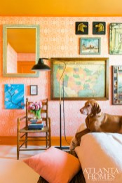 Meg's eclectic bohemian bedroom is layered with shades of coral and terracotta balanced by bright white painted floors. The Virginia-Highland home is located near plenty of green space ideal for her active vizsla, Huckleberry Flynn. Wallpaper, Tulsi Block Print in coral by Thibaut.