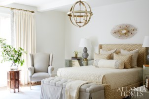 The serene master bedroom is an ode to the couple's love of nature. The custom Century bed features an animal-print fabric by Kelly Wearstler, while an antique copper-and-brass bird sculpture hangs overhead. Bedside tables, Bradley. Lamps, Bungalow Classic. Chandelier, Holland & Company.