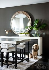 A hide rug anchors the center of the office, were the assembly of materials and ideas happens at a pewter-topped table by François & Co. and Holland and Company. Piper, Ferrier's pup, enjoys the soft texture.