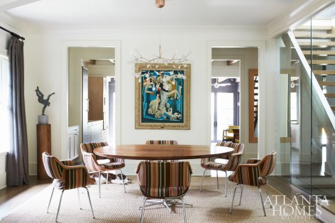In the dining room, vintage Kilta chairs by Finnish company Martela were upholstered in a bold Donghia fabric. A painting by prolific artist Jean de Botton and a whimsical chandelier from Switch Modern anchor the space. The bronze sculpture is by Martin Dawe of Cherrylion Sculpture Studios.
