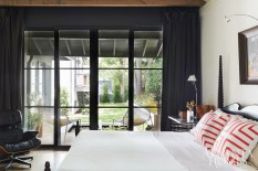 """The master bedroom is also a testament to the couple's minimalist aesthetic. """"It probably comes from being architects,"""" notes Dixon. """"We don't like a lot of extra things around the house, and we use everything that we have, so we're very careful in selecting nice, comfortable pieces and great artwork that really speaks to us."""" The glass doors were fabricated by Kolbe & Kolbe."""