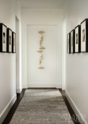 In a hallway, a sculpture by Maren Kloppmann through Signature Contemporary Craft pops next to photographs by Michael Kenna through Jackson Fine Art.