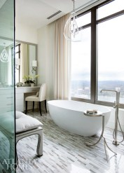 In the master bath, light touches, such as a cast acrylic chandelier by Porta Romana through Jerry Pair, Dmitriy's Brugge Bench through R Hughes and a Helene Aumont counter chair, allow skyline views to take center stage.