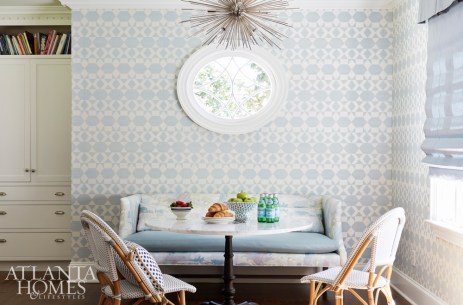 Phillip Jeffries' pale blue Zephyr wallcovering cultivates a fresh feel in the breakfast nook, where a sofa from Lee Industries—covered in Beacon Hill's Soo Locks and Kravet's Valera Spa fabrics—snuggles up to a marble-topped bistro table and chairs.