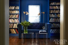 Glossy walls, painted Benjamin Moore's Patriot Blue, look extra posh when paired with a C.R. Laine tufted sofa upholstered in a matching Martin Sapphire fabric.