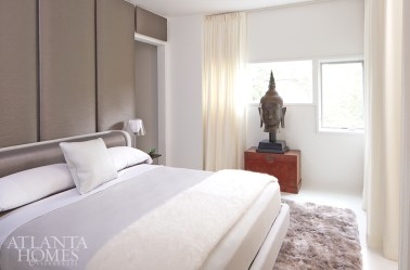 In contrast to the rest of the condo, the bedroom boasts a noticeable lack of color and a sense of softness, thanks to a sheepskin rug from Auskin and wall panels upholstered by Tecnosedia in an Armani/Casa fabric. Buddha sculpture, Mandarin Antiques. Lamps, Ktribe T by Flos. Bedding, custom.