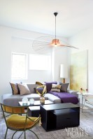 The designers continued the purple and gold palette into the den, where a pendant lamp by Constance Guisset hangs above a custom sofa by MUSSO.