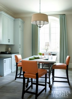 The homeowner, an avid sewer, wanted a laundry room that doubled as a craft space and a butler's pantry for catering services during parties, as it's right off the kitchen. Chairs covered in Kravet orange pleather, blue cabinetry, and faux-bois tiles on the floor create a sunny disposition throughout the multifaceted space.